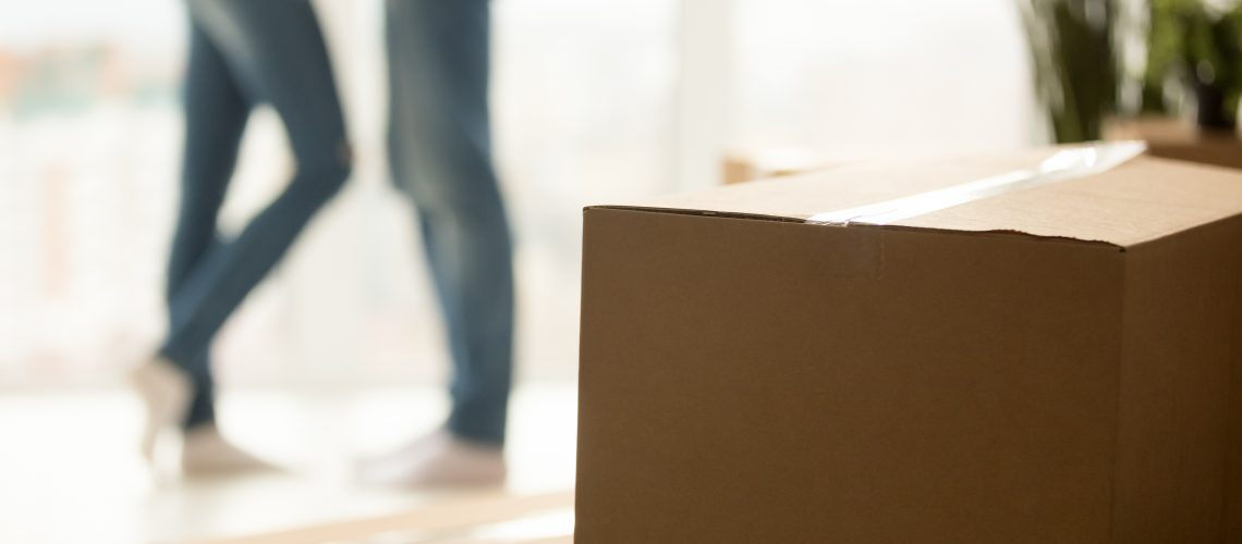 Close up of cardboard boxes and millennial couple in background hugging excited to move to new purchased apartment, young husband and wife relocating, starting living together in own home.